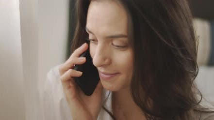 Thumbnail for Close up of a woman in white shirt talking to someone on the phone and smiling,
