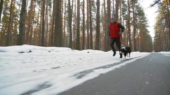Thumbnail for Man and Dog Jogging on Snowy Road