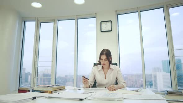 Thumbnail for Girl in a Business Suit Working in the Office Sitting at the Table