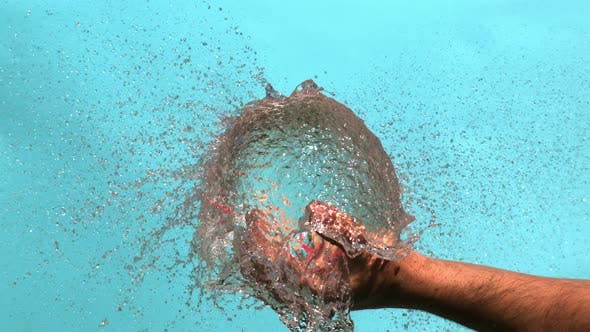 Exploding Of Red Water Balloon In A Palm Bursting With Drops On A Blue Background In High Speed