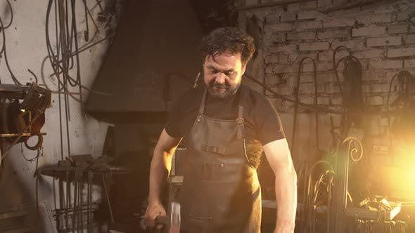Blacksmith Forges on the Anvil. Brutal Man Working at the Forge with Metal.