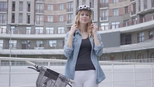 Thumbnail for Pretty Blond Woman Putting a Bike Helmet on Her Head and Riding Her Bicycle Against the Background
