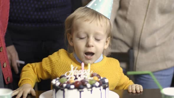 Cover Image for Toddler Boy Blows Candles on His Birthday at Home