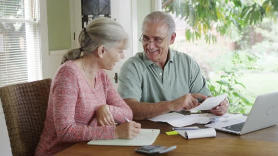 Thumbnail for Senior couple paying bills together on laptop