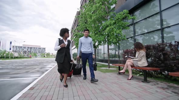 Cover Image for Business Travelers Walking with Suitcases in Downtown