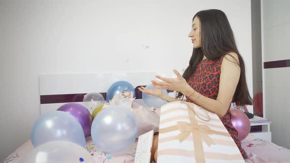 Side View of Woman Sitting on Bed with Colorful Balloons and Opens Confetti Bomb Birthday Card