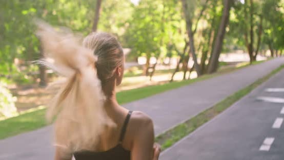 Thumbnail for Active Blonde Girl Jogging on Special Training Path in Public Park Early in Morning