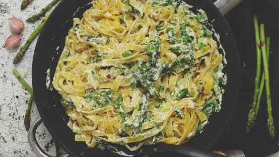 Tagliatelle Pasta with Ricotta Cheese Sauce and Asparagus Served on a Black Iron Pan