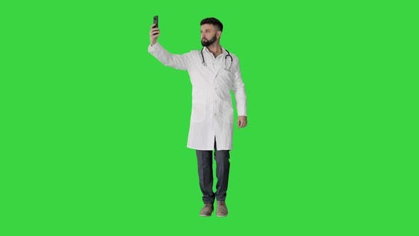Thumbnail for Doctor Taking a Selfie with Smartphone While Walking on a Green Screen, Chroma Key.