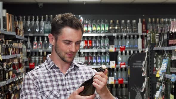 Thumbnail for Handsome Young Man Smiling To the Camera While Choosing Wine
