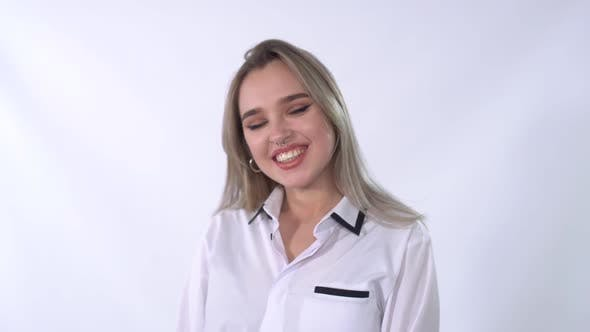 Thumbnail for Portrait of a Young Woman with Piercing in the Nose in a White Shirt Smiling at the Camera Close-up
