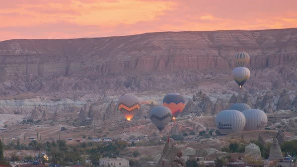 Colorful hot air balloons flying over the valley at sunrise time Goreme, Cappadocia, Turkey