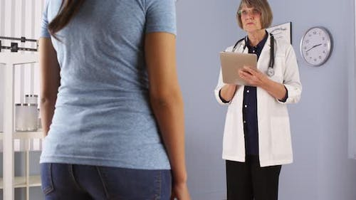 Senior doctor talking with overweight patient