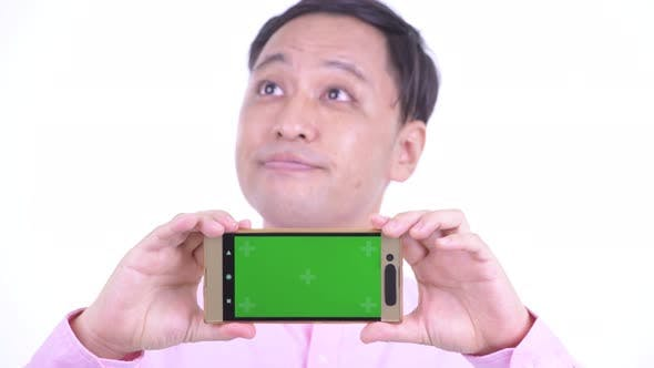 Thumbnail for Face of Happy Japanese Businessman Thinking While Showing Phone