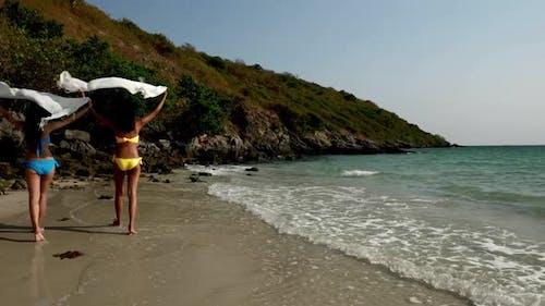 Rear view of young women in bikini with fabric walking on the beach