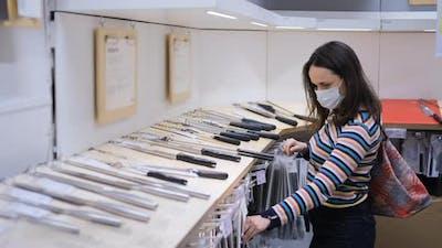 Woman Choosing Kitchen Knife in Furniture Store