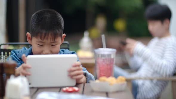 Thumbnail for Cute Asian Boy Playing on Digital Tablet in Outdoor Cafe