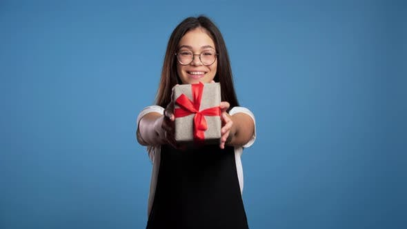 Thumbnail for Pretty Brunette Asian Girl in Glasses Gives Gift and Hands It To the Camera. She Is Happy