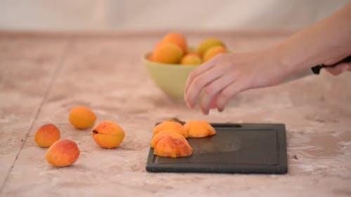 Female Hands Cutting Fresh Sweet Apricot