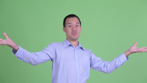 Thumbnail for Studio Shot of Happy Asian Businessman with Surprise Gesture