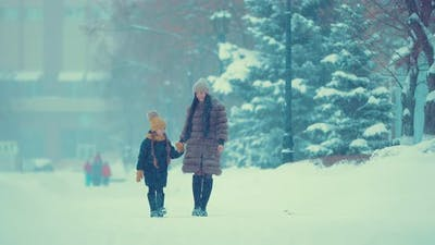 Mom and Daughter are Walking in the Snow