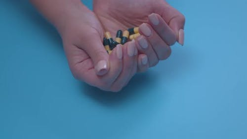 Closeup of a Woman's Hands with a Handful of Pills