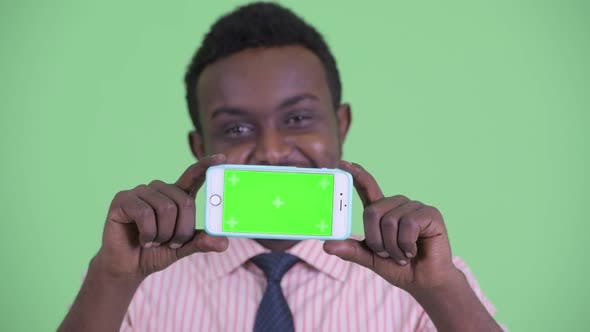 Thumbnail for Face of Happy Young African Businessman Thinking While Showing Phone