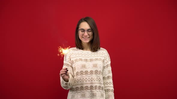 A Young Woman in a White Sweater Holds a Sparkler in Her Hand. Shooting in the Studio on a Red