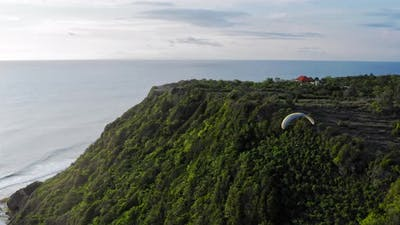Paraplane, Paraglider In The Air Aerial Shot. Extreme Man Flies On a Paraglider Over a Cliff Near