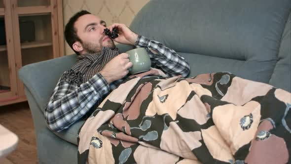 Thumbnail for Sick Young Man Drinking Hot Tea or Anti-fever Medicine in Bed