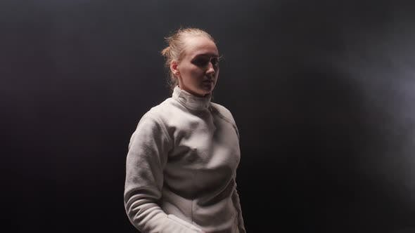 Thumbnail for A Young Woman Fencer in the Dark Smoky Studio