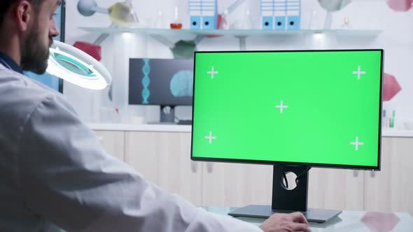 Thumbnail for Zoom in Shot of Doctor Working on Computer with Green Screen Mock-up
