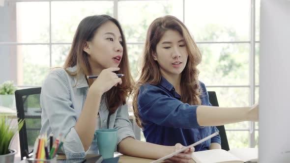 Asian business women in smart casual wear working on desktop while sitting on desk in office.