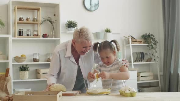 Thumbnail for Grandma and Girl with Down Syndrome Making Dough