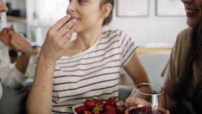 Zoom out video of friends chatting and eating seasonal strawberries