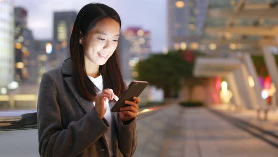 Thumbnail for Businesswoman use of cellphone at night