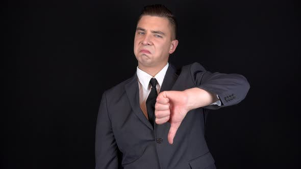 Thumbnail for Young Businessman Shows Dislike on Hand. Man in a Black Suit on a Black Background