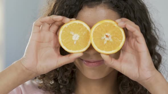 Thumbnail for Portrait of cheerful biracial woman applying halves of orange to eyes, optimism