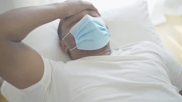 Thumbnail for Portrait of Sick African American Man in Face Mask Suffering From Fever. Ill Young Patient Lying in