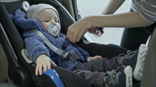 Mother Placing Baby into Car Seat