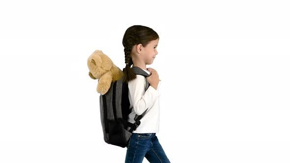 Cute Little Girl Walking To School with a Teddy Bear Sticking Out of Her Backpack on White