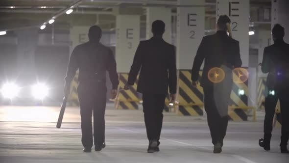Thumbnail for Four Confident Mafia Men in Black Suits Holding Baseball Bats and Walking Towards Car