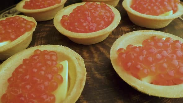 Thumbnail for Red Caviar Is Put with a Spoon on Tartlets. Preparation of Snacks with Red Caviar. Top View