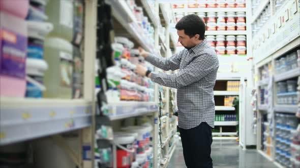 Man Choosing a Paint Bank in the Hypermarket
