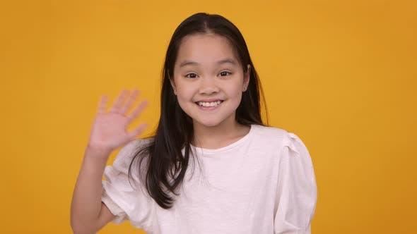 Cute Friendly Asian Girl Waving Hand Hi and Smiling To Camera Orange Studio Background