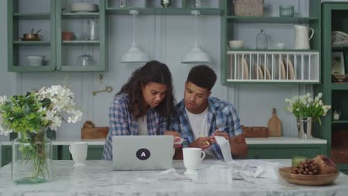 20s African American Couple Managing Family Budget Sitting on Kitchen
