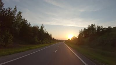 Driving along a rural road at sunset