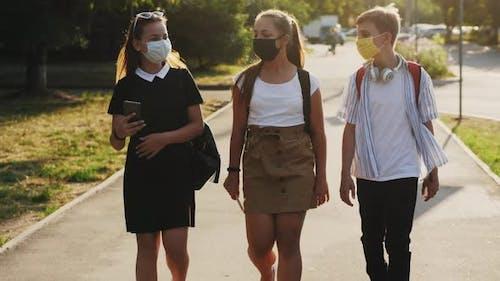 Schulkinder mit Gesichtsmasken gehen die Straße hinunter