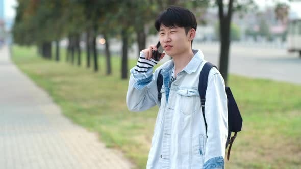 Thumbnail for Asian Teenager Having Phone Conversation Outdoors