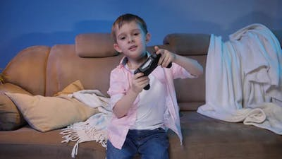 Funny Little Boy Holding Game Controller While Playing Video Games on TV Console at Night